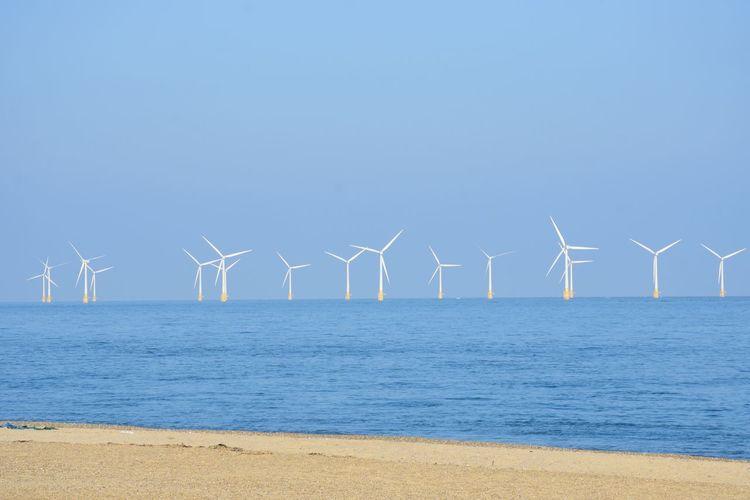 Wind turbines on beach against clear blue sky