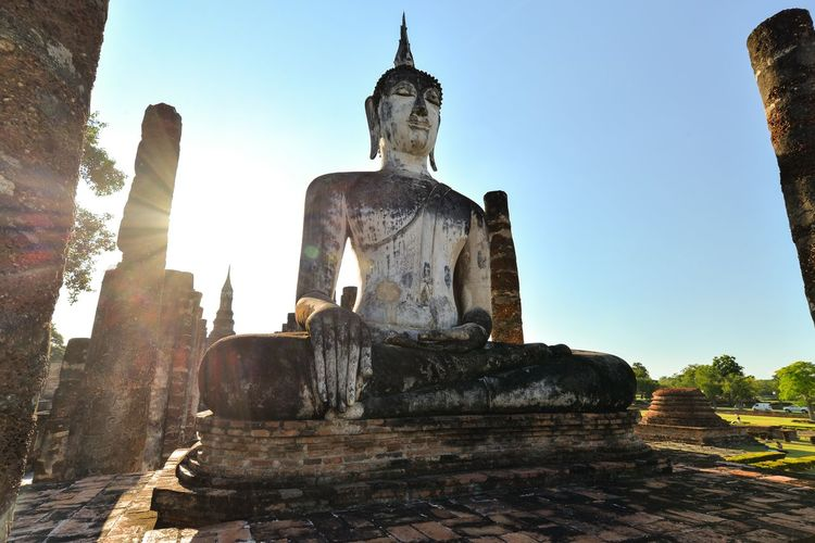 Thailand, Sukhotai, Archaeological site with temple ruins and Buddha statue Buddha Statue Sukhothai Thailand Temple Archaeological Buddha Religion Architecture Sky Spirituality Belief Art And Craft Sculpture Built Structure Outdoors Statue Low Angle View Clear Sky
