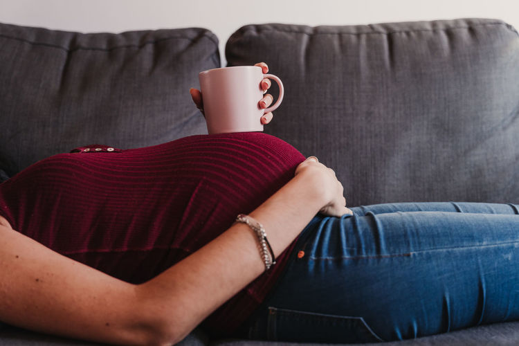 Midsection of pregnant woman with cup lying on sofa