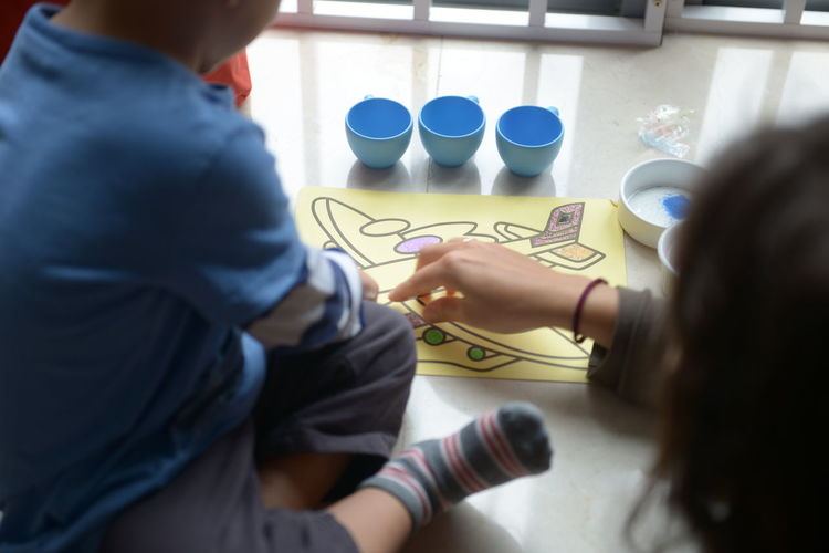 High angle view of mother and son coloring on table at home