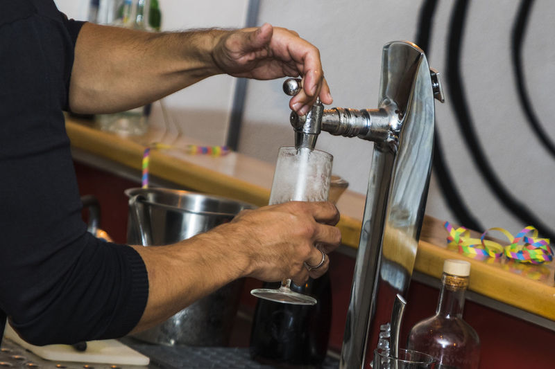 Midsection Of Man Filling Drink In Glass