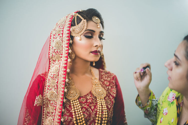 Close-Up Of Woman Applying Lipstick On Beautiful Bride Against White Background
