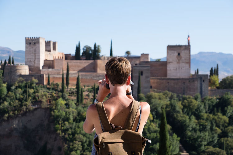 A tourist takes a picture of the Alhambra in Granada Spain Andalucía Capture The Moment Granada SPAIN Tourist Tourist Attraction  Trees View Alhambra Architecture Blond Hair Building Exterior Built Structure Leisure Activity One Person Outdoors People Photographer Real People Rear View Rucksack Standing Taking A Picture Tourist Destination Young Women
