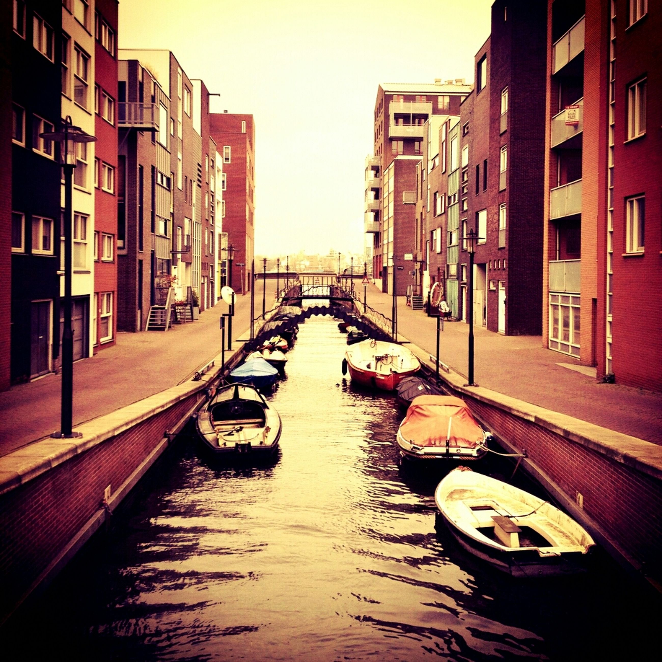 architecture, building exterior, built structure, water, canal, waterfront, building, residential structure, residential building, reflection, nautical vessel, city, transportation, boat, mode of transport, moored, house, sky, rippled, diminishing perspective
