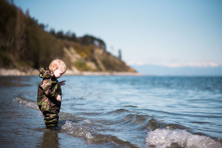 Beach Beauty In Nature Blond Hair Boys Camouflage Clothing Childhood Clear Sky Comoxvalley Day Full Length Fun Leisure Activity Lifestyles Nature One Boy Only One Person Outdoors People Real People Sea Sky Standing Vancouver Island Water