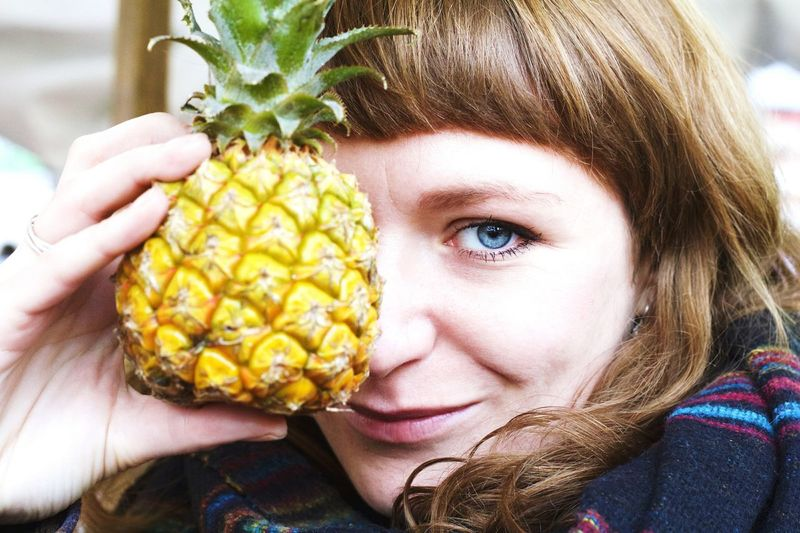 Close-up portrait of smiling young woman showing pineapple