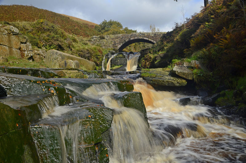 Water flowing through arch bridge over river