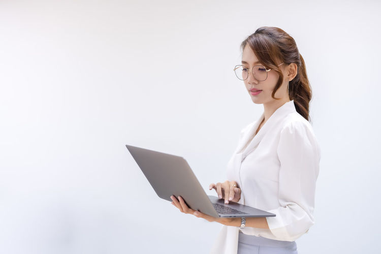 Young woman using mobile phone against white background