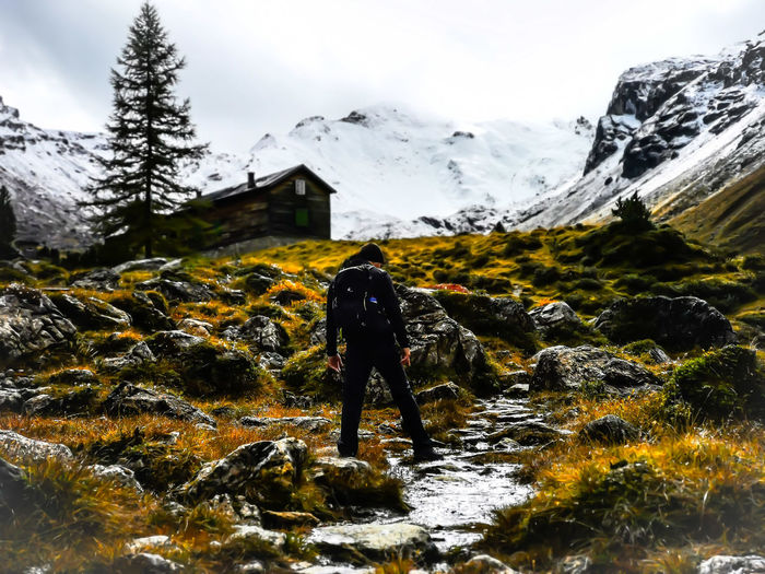 Rear view of person walking on snowcapped mountain