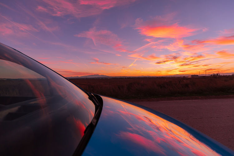 Cropped image of car against sky during sunset