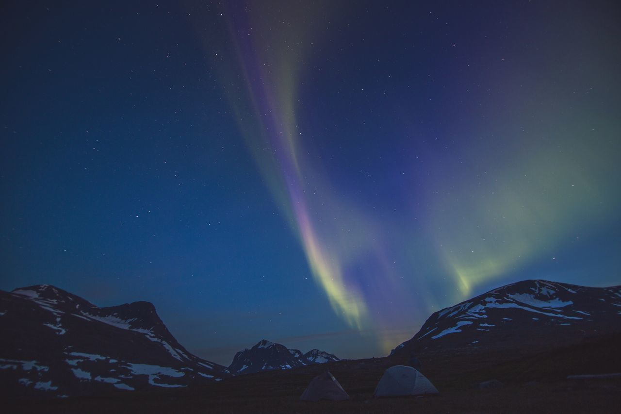 Camping tents by mountains against sky with aurora borealis