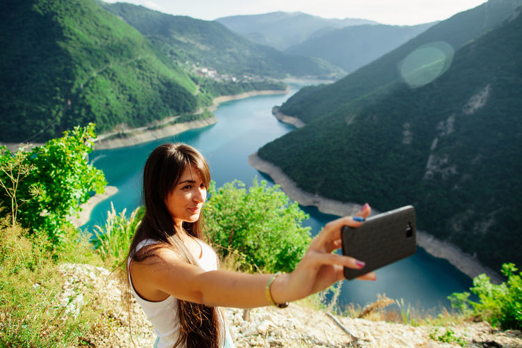 woman travel with smart phone and taking selfie photo EyeEm Best Shots Beauty In Nature Casual Clothing Day Lake Landscape Leisure Activity Lifestyles Looking At Camera Mountain Nature One Person Outdoors Portrait Real People Scenics Selfie Smart Phone Smartphonephotography Smiling Standing Tranquil Scene Tranquility Water Young Adult