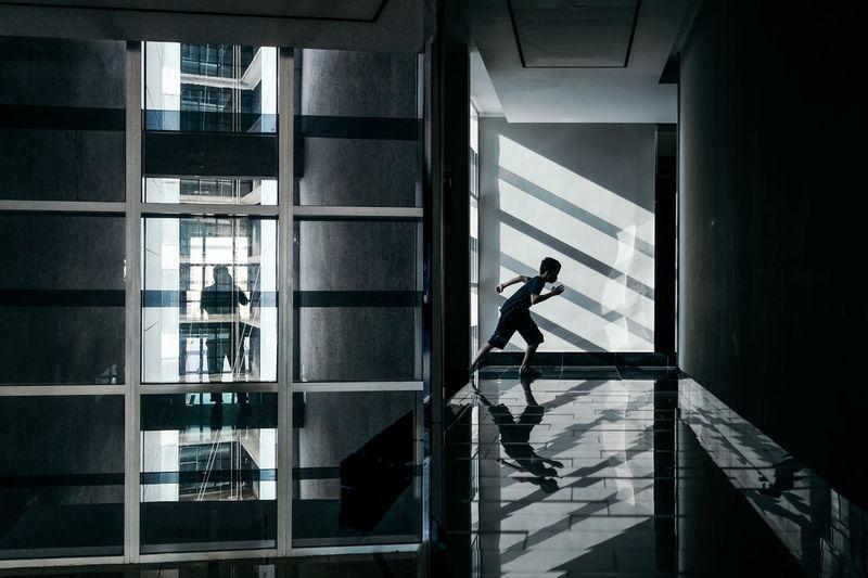Side view of teenage boy running on floor