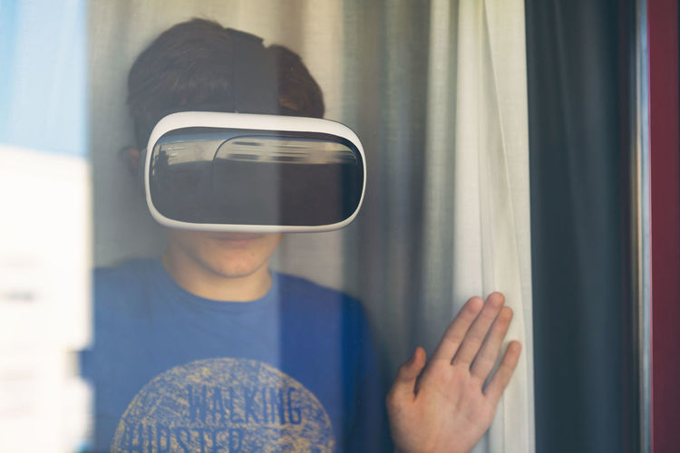 Teenage boy wearing virtual reality simulator