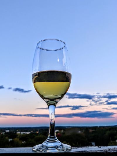 Close-up of wineglass on retaining wall against sky during sunset