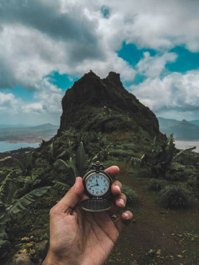 Cropped Hand Holding Pocket Watch Near Mountain Against Cloudy Sky