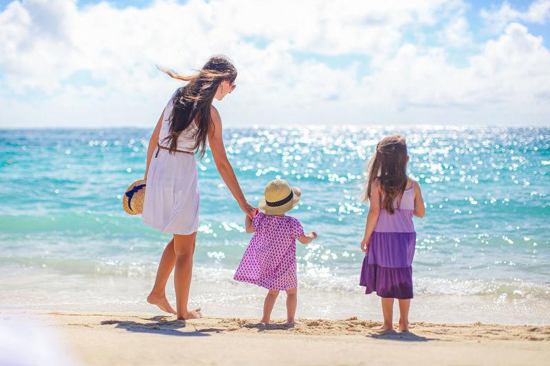 Rear view of women standing on beach