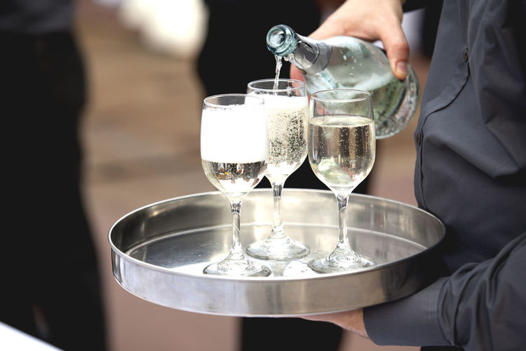 Midsection of waiter pouring wine in glasses
