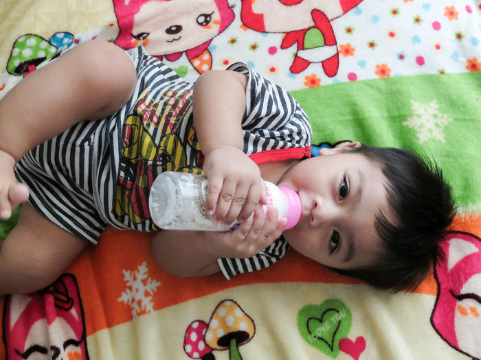 Portrait of cute boy drinking milk from baby bottle while lying on bed at home