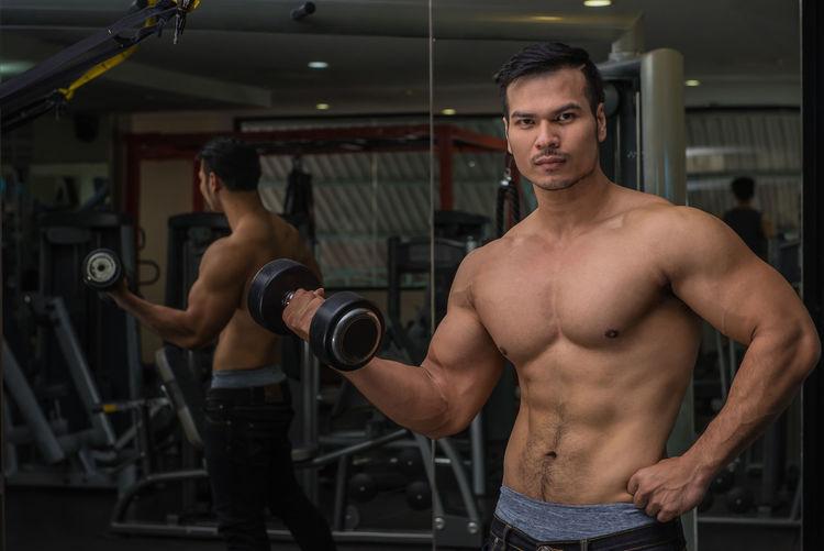 Portrait of shirtless muscular man exercising at gym