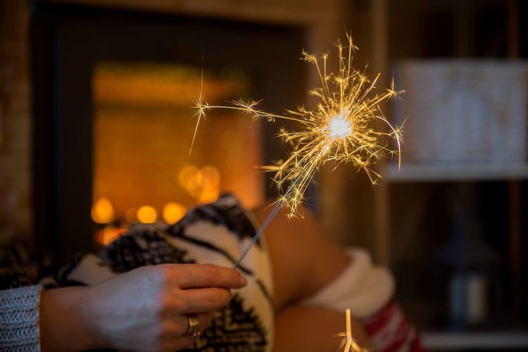 Woman hand holding sparkler on fireplace background Burning Blurred Motion Holding One Person Hand Sparkler Firework Human Hand Sparks Illuminated Motion Fireplace Fireplace Time Sparkle Sparkler Sparklers Cozy Blanket Winter Wintertime Holidays Season  Cabin New Year New Year's Eve