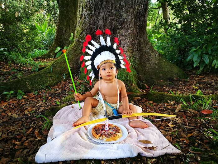 Baby Boy Wearing Traditional Headdress While Sitting With Birthday Cake Against Tree In Forest