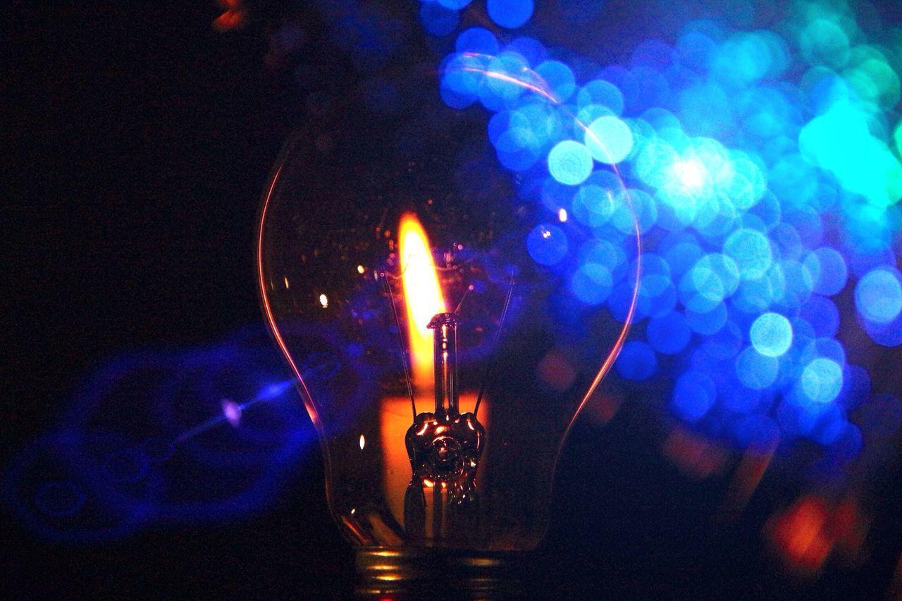 Light bulb against candle