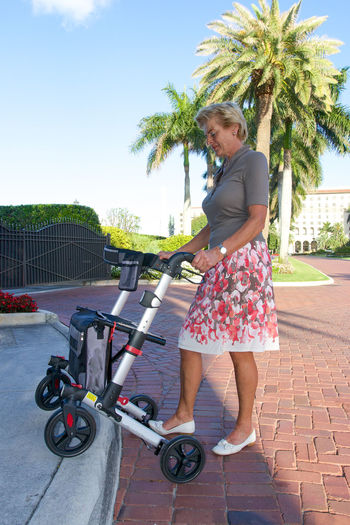 Woman walking with walker in Palm Beach, FL Adult Adults Only Assisted Blue Elderlyu Handicraft One Person Outdoors Park People Retired Retirement Rolla Safe Sea Sen Sky Smile Snowbidr Sunny Sunset Women