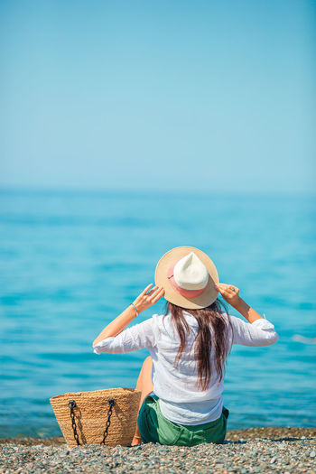 Rear view of woman in hat by sea against sky