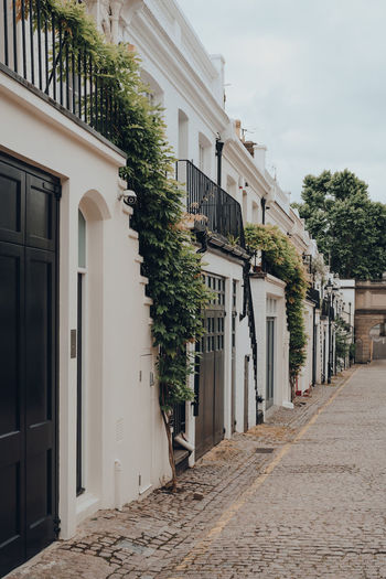 Facade of a typical row of mews houses with garages in london, uk. real estate and property concept.