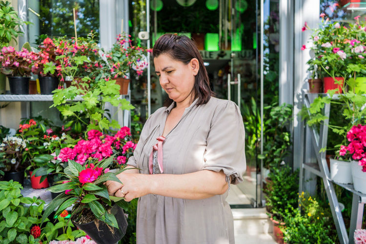 Woman Holding Potted Flower In Plant Nursery