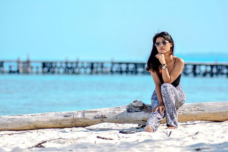 Full length of woman sitting on fallen tree trunk at beach against sky