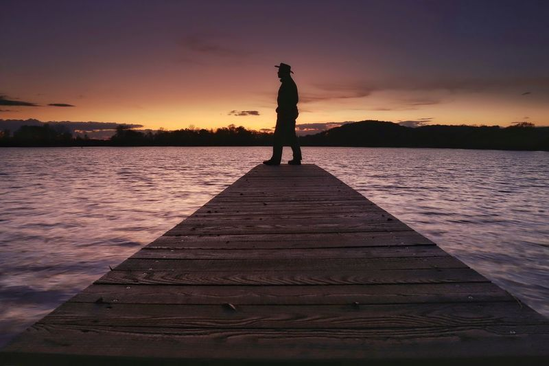 """Enjoying the view"" Sunset Water Pier Lake One Person Jetty Full Length Sky Tranquil Scene Beauty In Nature Outdoors Real People Nature Scenics Leisure Activity Wood - Material Standing Tranquility Silhouette Lifestyles Enjoying The View Michael Hruschka Sunset_collection Cowboy Cowboy Hat"