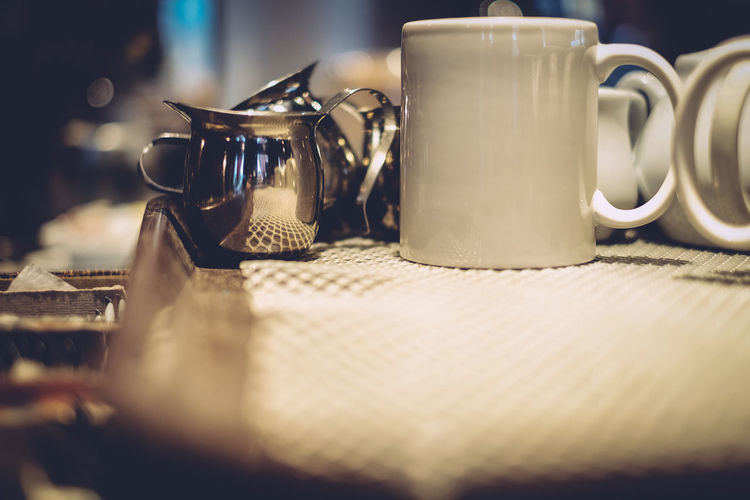 Close-up of cups and jugs on table at restaurant