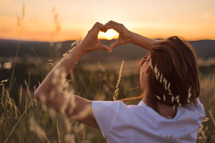 Rear view of woman making heart shape against sky during sunset