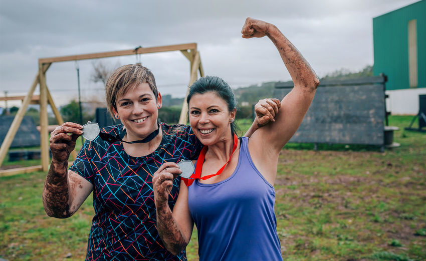 Happy sporty friends showing medals while exercising on land