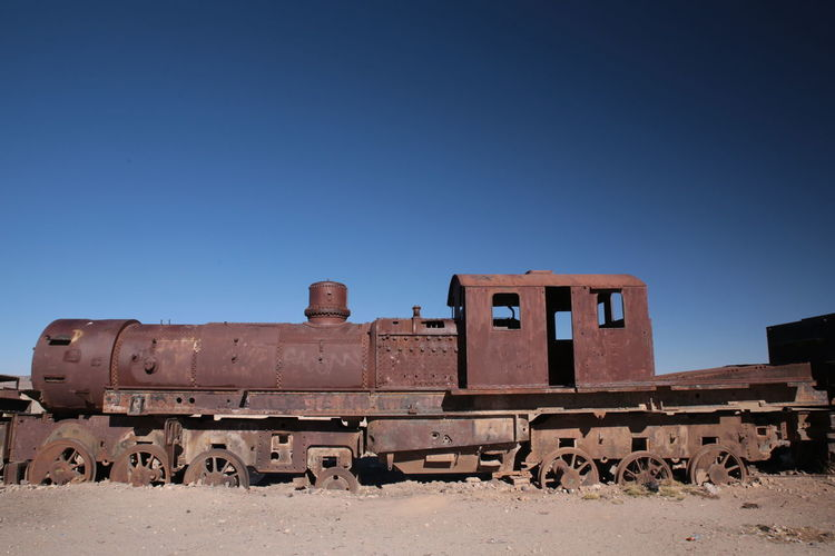 Abandoned train against clear blue sky