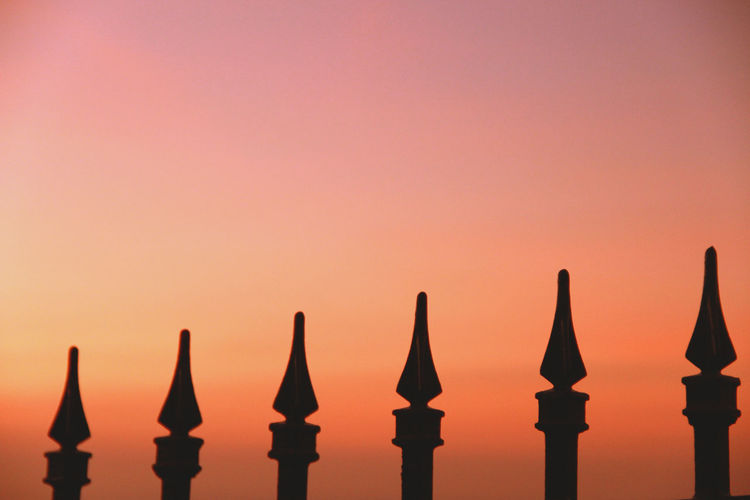 Close-Up Of Fence Against Sky During Sunset