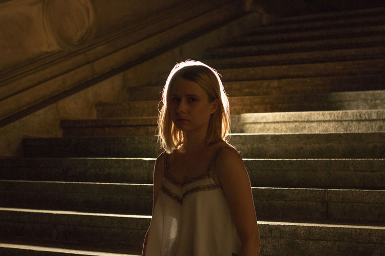 Full length of young woman sitting on steps at night