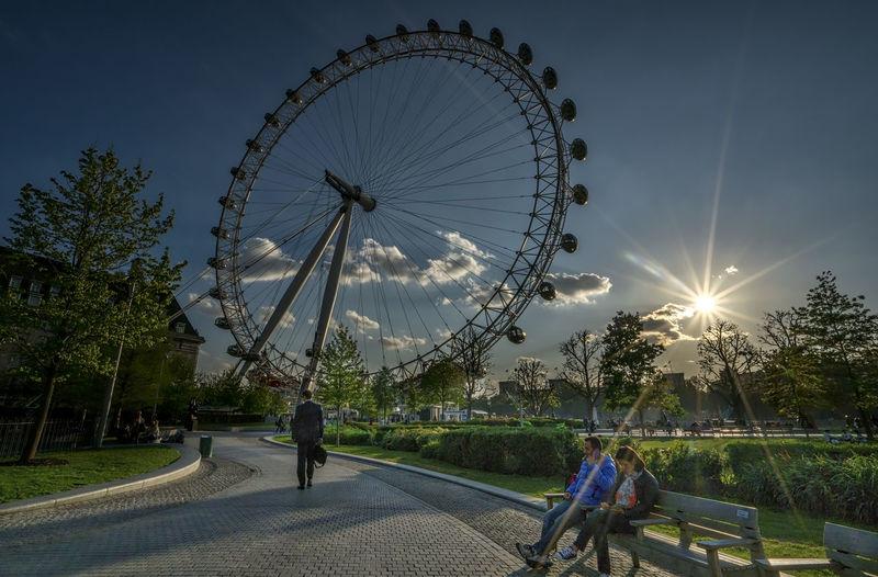 Sun shining through ferris wheel in city