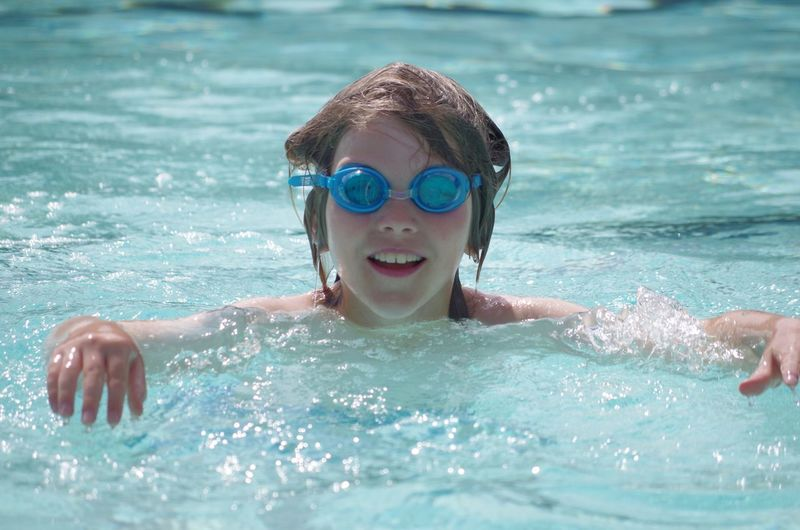 Happy boy wearing swimming goggles enjoying at pool