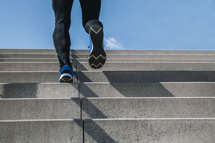 Young man exercising climbs stairs outdoors. cut the view of strong and powerful legs