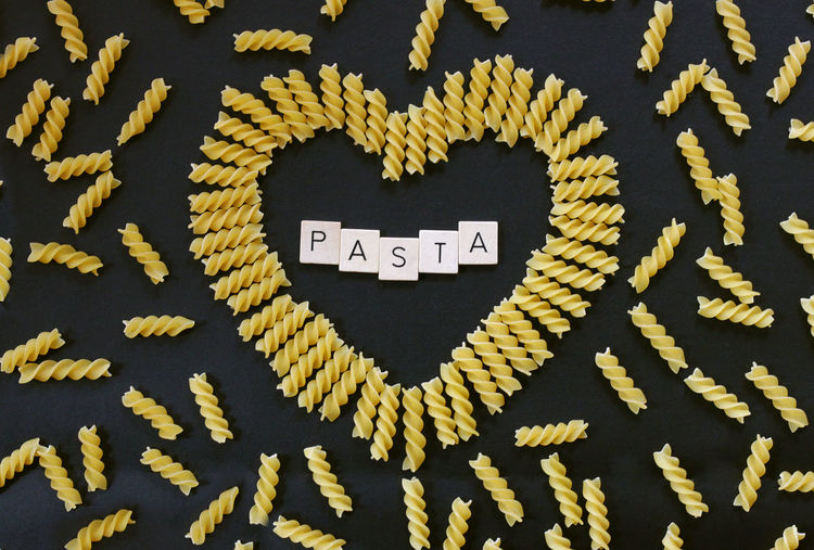 Directly Above View Of Text Amidst Heart Shape Pasta