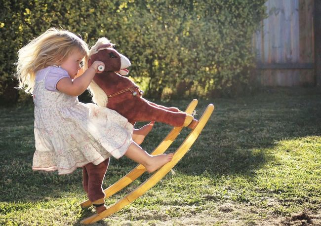Sunlit Glow Childhood Rocking Horse Blond Hair Outdoors Child Summer Girl Little Girl SeriousBusiness Serious Business Funny Riding Toddler  Facial Expressions Adrenaline Junkie Cute Fun Happiness Children Only EyeEmNewHere Real People Break The Mold