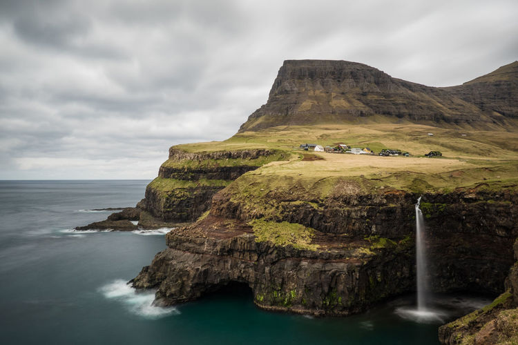 Scenic view of cliffs by sea against cloudy sky