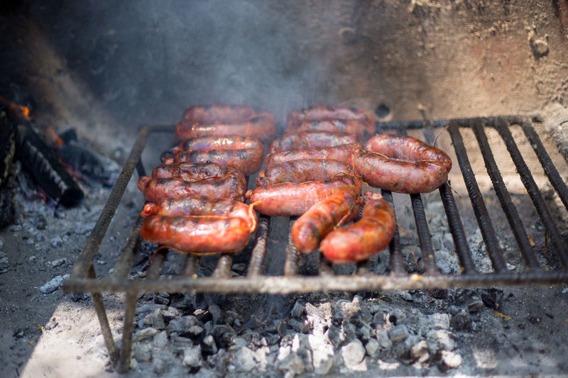 High angle view of chorizo grilling on barbecue