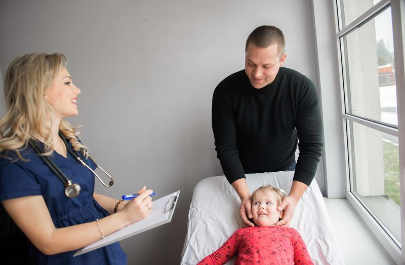 At the doctor Young Adult Doctor  Kid Child Girl Dad Faamily Visit Medical Medical Equipment Exam Examining Pediatrician Pediatrics Sick Kid Sick Illness Disease Health Medicine Proffesional Female Stethoscope  Office Clinic Room Insurance Natural Light Family Consulting Vaccine Vaccination Little Girl Smiling Serious People At The Doctor Family Doctor Day Horizontal Color Image Bright Background Gray Blue Casual