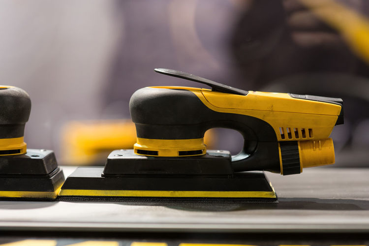 Close-up of yellow machine on table