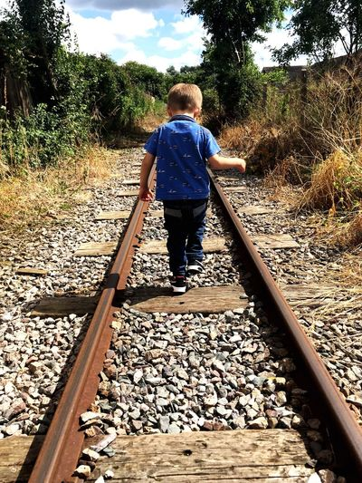 Railroad Track Full Length Stone - Object Transportation Casual Clothing Rail Transportation Tree Walking The Way Forward Gravel Rear View Pebble Leisure Activity Day Person Outdoors Diminishing Perspective Toddler  Surface Level Countryside