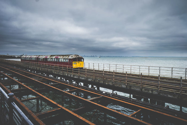 Train on railroad tracks by sea against sky